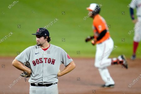 Boston Red Sox relief pitcher Josh Taylor, left, as Baltimore Orioles' Anthony Santander, right, runs the bases after hitting a two-run home run off him during the eighth inning of a baseball game, in Baltimore. The Orioles won 5-4 in ten innings