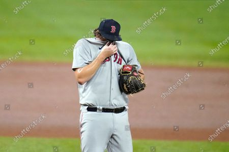Stock Picture of Boston Red Sox relief pitcher Josh Taylor wipes sweat between pitches to Baltimore Orioles' Anthony Santander during the eighth inning of a baseball game, in Baltimore