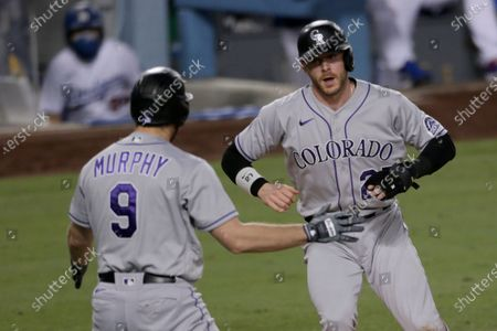 Colorado Rockies shortstop Trevor Story, right, celebrates scoring with Daniel Murphy during the sixth inning of a baseball game against the Los Angeles Dodgers in Los Angeles