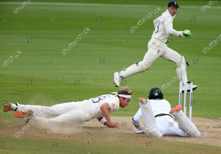 England's Stuart Broad, left, makes an unsuccessful attempt to run-out Pakistan's captain Azhar Ali, right, during the third day of the third cricket Test match between England and Pakistan, at the Ageas Bowl in Southampton, England