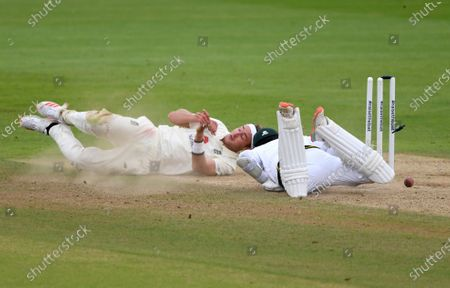 England's Stuart Broad, left, collides with Pakistan's captain Azhar Ali in an unsuccessful run-out attempt during the third day of the third cricket Test match between England and Pakistan, at the Ageas Bowl in Southampton, England