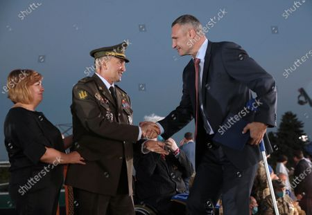 Kyiv city head Vitali Klitschko (R) shakes hands with chief of Ivan Bohun Kyiv Military Lyceum, Hero of Ukraine Ihor Hordiichuk during the ceremony of hoisting the largest Ukrainian flag (16 by 24 metres) on the 90m(295ft) tall flagpole at the National Museum of the History of Ukraine in WWII Memorial Complex, Kyiv, capital of Ukraine.