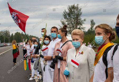 "Former Lithuanian President Dalia Grybauskaite, second from right, and other supporters of Belarus opposition participate in a ""Freedom Way"", a human chain of about 50,000 strong from Vilnius to the Belarusian border, during a protest near Medininkai, Lithuanian-Belarusian border crossing east of Vilnius, Lithuania, . In Aug. 23, 1989, around 2 million Lithuanians, Latvians, and Estonians joined forces in a living 600 km (375 mile) long human chain Baltic Way, thus demonstrating their desire to be free. Now, Lithuania is expressing solidarity with the people of Belarus, who are fighting for freedom today"
