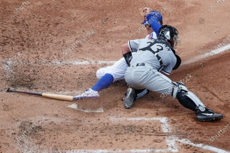 Chicago White Sox catcher James McCann, right, tags out Chicago Cubs first baseman Anthony Rizzo, left, at home plate during the fourth inning of a baseball game, in Chicago