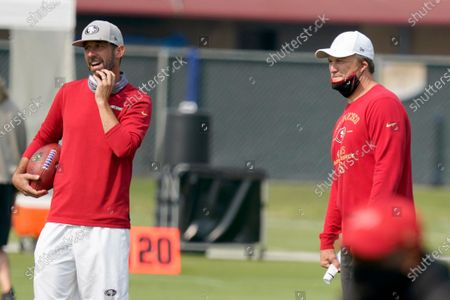 San Francisco 49ers general manager John Lynch, right, and head coach Kyle Shanahan watch players warm up during NFL football practice at the team's training facility in Santa Clara, Calif