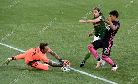 Portland Timbers goalkeeper Steve Clark, left, blocks the shot of Seattle Sounders forward Raul Ruidiaz, right, as Portland Timbers' Jorge Villafana, center, defends during the first half of an MLS soccer match in Portland, Ore