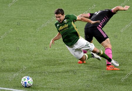Portland Timbers forward Tomas Conechny, left, is tripped by Seattle Sounders defender Gustav Svensson during the second half of an MLS soccer match in Portland, Ore., . Seattle won 3-0