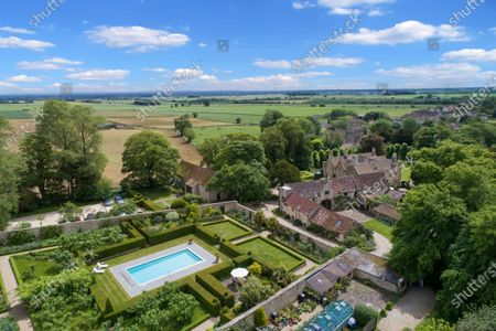 Bird's eye view of the house, gardens and pool.   A stunning Georgian house that comes with its own separate office buildings including an impressive boardroom is on the market for £6.5m.  The grand-looking Tormarton Court is a classic country house with plenty of period features, set in 10 acres of grounds, perfect for those looking to escape city life.  But it also comes with an array of outbuildings ideal for setting up your business from the comfort of your back garden, making the daily commute much easier.  Nestled in the Cotswold countryside, the new owner will be in good company with billionaire entrepeneur James Dyson and the Duke of Beaufort as neighbours.