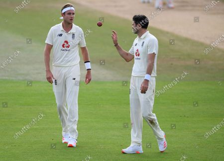 England's James Anderson, right, receives the ball from teammate Stuart Broad during the fourth day of the third cricket Test match between England and Pakistan, at the Ageas Bowl in Southampton, England