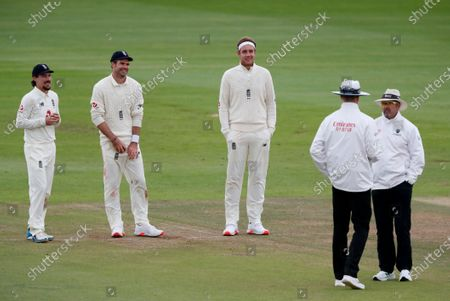 England players, from left, Rory Burns, James Anderson and Stuart Broad smile as they watch umpires discuss about light conditions during the fourth day of the third cricket Test match between England and Pakistan, at the Ageas Bowl in Southampton, England