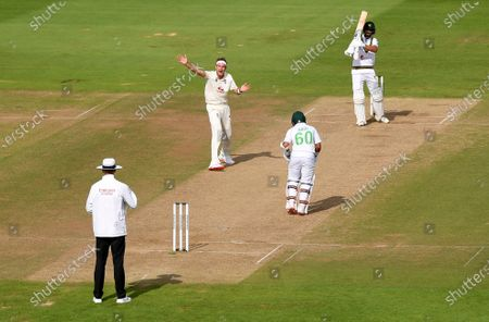 Stock Photo of England's Stuart Broad, center left, appeals successfully for the wicket of Pakistan's Shan Masood, right, during the fourth day of the third cricket Test match between England and Pakistan, at the Ageas Bowl in Southampton, England
