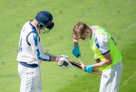 Yorkshire's George Hill has running bat repairs made by team mate James Logan.
