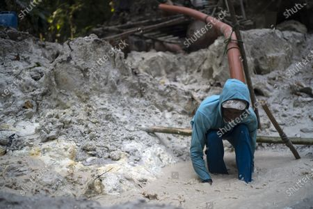 Zé Preto searches for debris that could clog the suction pump in a ravine at an illegal gold mine in the Amazon jungle in the Itaituba area of Para state, Brazil, . It's part of a gold rush that started in 1984 after the precious metal was discovered in the region, where around 30 tons of gold worth some $1.1 billion are illegally traded in the state of Para annually, according to National Mining Agency estimates, or about six times more than the amount legally declared