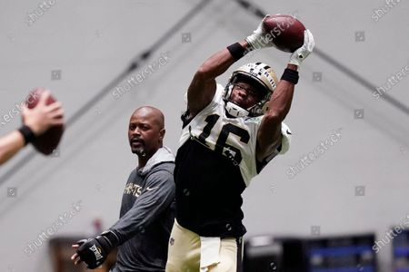 Stock Picture of New Orleans Saints wide receiver Bennie Fowler (16) catches a pass in front of wide receivers coach Ronald Curry during practice at their NFL football training facility in Metairie, La