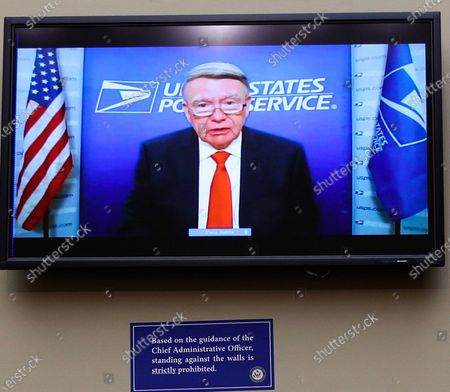 United States Postal Service Board of Governors President Robert Duncan is seen on a television monitor testifying remotely during a US House Oversight and Reform Committee hearing on slowdowns at the Postal Service ahead of the November elections on Capitol Hill in Washington, U.S.,.