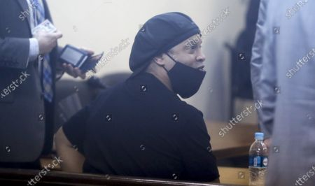 Former Brazilian soccer star Ronaldinho is seen through a pane of glass as he sits before a judge at the Justice Palace in Asuncion, Paraguay, . Ronaldinho and his brother have been detained since early March for allegedly entering the South American country with fake passports