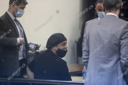 Former Brazilian soccer star Ronaldinho, center, is seen through a pane of glass as he sits before a judge at the Justice Palace in Asuncion, Paraguay, . Ronaldinho and his brother have been detained since early March for allegedly entering the South American country with fake passports