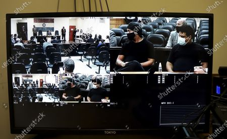 Television screen broadcasts a signal from the Supreme Court of Justice of Paraguay, that shows former Brazilian soccer star Ronaldinho and his brother Roberto de Assis, as they sit for a court date at the Justice Palace in Asuncion, Paraguay, . Ronaldinho and his brother have been detained since early March for allegedly entering the South American country with fake passports
