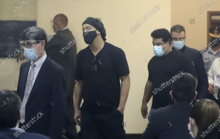Former Brazilian soccer star Ronaldinho, center, and his brother Roberto Assis, center right, are seen entering through a pane of glass during a court date at the Justice Palace in Asuncion, Paraguay, . Ronaldinho and his brother Roberto Assis have been detained since early March for allegedly entering the South American country with fake passports