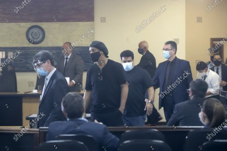 Former Brazilian soccer star Ronaldinho, center left, and his brother Roberto Assis, center right, are seen through a pane of glass during a court date at the Justice Palace in Asuncion, Paraguay, . Ronaldinho and his brother Roberto Assis have been detained since early March for allegedly entering the South American country with fake passports