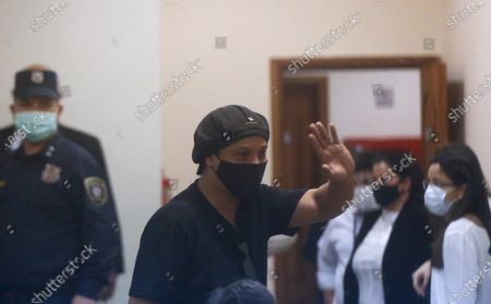 Former Brazilian soccer star Ronaldinho, seen through a pane of glass, waves during a court date at the Justice Palace in Asuncion, Paraguay, . Ronaldinho and his brother Roberto Assis have been detained since early March for allegedly entering the South American country with fake passports