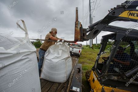 (L-R) Aureland Moak helps Darren Anderson unload sand bags in Belle Chasse, Louisiana, USA, 24 August 2020. South Louisiana is bracing for the impact of two storms in one week with Tropical Storm Marco make landfall later on the same day and Tropical Storm Laura predicted to make landfall as a hurricane along the Louisiana and Texas coastline on 27 August.