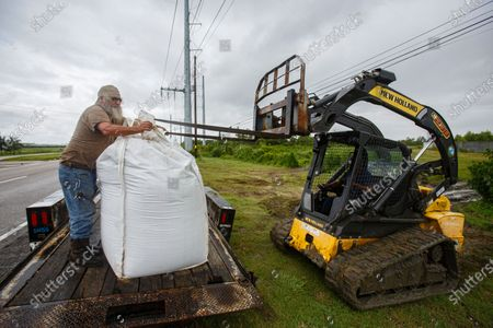 Stock Photo of (L-R) Aureland Moak helps Darren Anderson unload sand bags in Belle Chasse, Louisiana, USA, 24 August 2020. South Louisiana is bracing for the impact of two storms in one week with Tropical Storm Marco make landfall later on the same day and Tropical Storm Laura predicted to make landfall as a hurricane along the Louisiana and Texas coastline on 27 August.