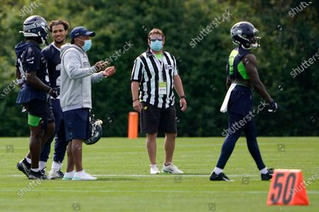 Seattle Seahawks general manager John Schneider, center, wears a referee shirt as players walk off the field after NFL football training camp, in Renton, Wash. Due to concerns and tight controls surrounding the coronavirus pandemic, the usual referees who work during training camp sessions have not been a part of practices this season, so team personnel, including Schneider, have been dressing in the uniform and making calls as players run drills