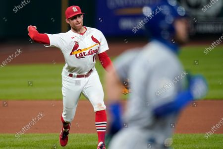 St. Louis Cardinals third baseman Brad Miller, left, commits a throwing error allowing Kansas City Royals' Alex Gordon, right, to reach base during the fifth inning of a baseball game, in St. Louis