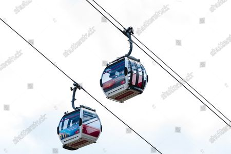 Two Cole cars pass on the Emirates Air Line link across the River Thames in London.