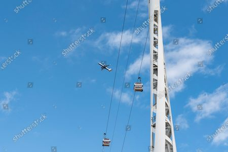 An airplane from London City Airport flies above the Emirates Air Line cable car link across the River Thames in London.