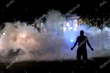 Protester attempts to continue standing through a cloud of tear gas fired by police outside the Kenosha County Courthouse, late, in Kenosha, Wis. Protesters converged on the county courthouse during a second night of clashes after the police shooting of Jacob Blake a day earlier turned Kenosha into the nation's latest flashpoint city in a summer of racial unrest