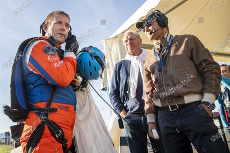 Stock Image of Swiss adventurer Raphael Domjan (L) reacts with wiss Pilot Bertrand Piccard (R), initiator and chairman of the Solar Impulse project, upon landing after he jumped with a parachute from the SolarStratos solar powered aircraft prototype with Spanish test pilot Miguel A. Iturmendi aboard during a test flight and attempt to break two world records at the airbase in Payerne, Switzerland, 25 August 25, 2020. Two world record were made during the test flight, the first jump in history from an electric aircraft exclusively charged with solar energy and the first solar free fall. The main objective of the SolarStratos Mission project is to be the first solar flight to achieve stratospheric flight.
