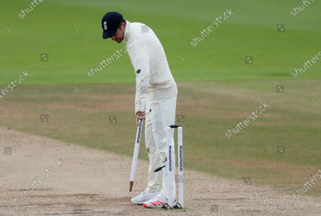 England's James Anderson pulls out a stump at the end of the fifth day of the third cricket Test match between England and Pakistan, at the Ageas Bowl in Southampton, England