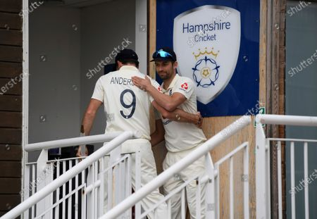England's Mark Wood, right, hugs to congratulate teammate James Anderson at the end of the fifth day of the third cricket Test match between England and Pakistan, at the Ageas Bowl in Southampton, England