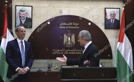 Palestinian Prime Minister Mohammad Ishtayeh, gestures to British Foreign Secretary Dominic Raab during a press conference in the West Bank City of Ramallah, . Portraits of Palestinian President Mahmoud Abbas, right and the llat Palestinian leader Yasser Arafat hangs in background