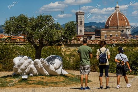 Give by a new work Lorenzo Quinn, a Roman artist, is previewed in the Gardens with the back drop of the Duomo - Visitors return to see the Boboli Gardens and the varied sights of the historic city of Florence following the easing of Coronavirus (covid 19) travel restrictions.