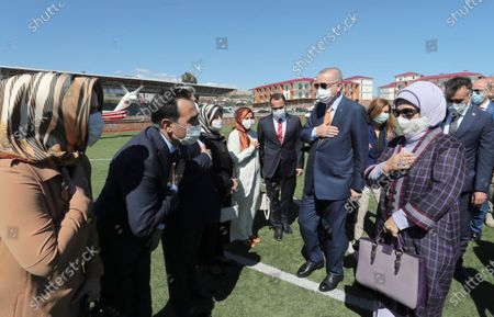 Officials welcome Turkey's President Recep Tayyip Erdogan, center, and his wife Emine Erdogan, right, at the airport, in Van, Turkey, . Erdogan on Tuesday revealed a new presidential summer residence in Ahlat, on the shores of Lake Van. The mansion was built despite opposition accusations that public funds were being squandered