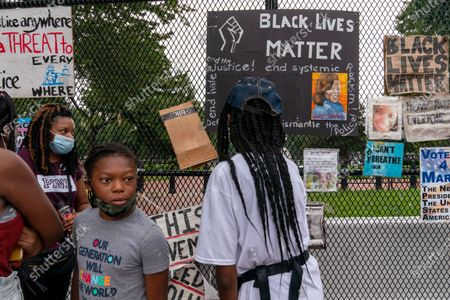"Wearing a shirt that says, ""Our generation will change the world,"" Jordan Brown, 8, of Baltimore, left, visits a fence near the White House that's been covered in protest posters, as he and his family visit a section of 16th Street, Northwest, renamed Black Lives Matter Plaza,, in Washington. ""We wanted to take them here so they can learn the history of what's been going on and is still going,"" says Brown's aunt, Shari Moore, far left, ""innocent lives are being taken"