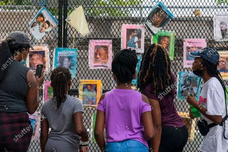 "From left, Melissa Brooks, Jordan Brown, 8, Jazmine Brooks, 9, Shari Moore, and Laila Brooks, 14, all of Baltimore, look at photographs of people who were killed by police that cover a fence near the White House, as the family visit a section of 16th Street, Northwest, renamed Black Lives Matter Plaza,, in Washington. ""We wanted to take them here so they can learn the history of what's been going on and is still going,"" says Shari Moore, who came to the site with her sister and their children, ""innocent lives are being taken"