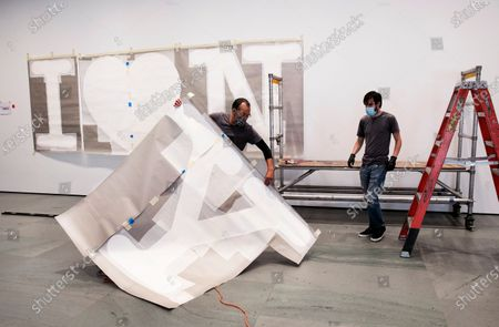 """Stock Photo of George Vealsquez, left, and Charles Lester install templates for """"I Love NY"""" at the entrance to the Museum of Modern Art, in New York. The work by graphic designer Milton Glaser will be done in red for the heart and black for the lettering. MOMA reopens Aug. 27, 2020"""