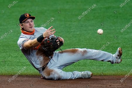 Baltimore Orioles shortstop Pat Valaika makes a diving stop but can't throw out Tampa Bay Rays' Mike Zunino at second base on a single by Michael Brosseau during the second inning of a baseball game, in St. Petersburg, Fla