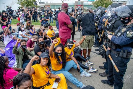 Stock Image of Tiffany Hicks, from left, Yandy Smith and Porsha Williams sit down in front of police during the Good Trouble Tuesday march for Breonna Taylor,, in Louisville, Ky