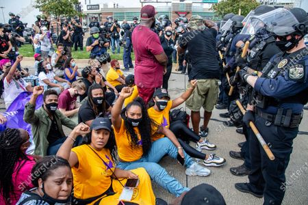 Stock Picture of Tiffany Hicks, from left, Yandy Smith and Porsha Williams sit down in front of police during the Good Trouble Tuesday march for Breonna Taylor, in Louisville, Ky