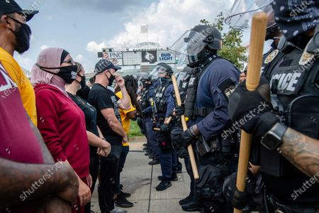 Stock Picture of Activist Linda Sarsour, center, stands in front of police officers as they stand guard during the Good Trouble Tuesday march for Breonna Taylor, in Louisville, Ky