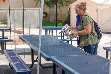 Lisa Peterson applies a non-toxic cleaner on lunch tables prior to the students lunch break at Christian Unified on Monday, Aug. 24, 2020 in El Cajon, CA. The seats have X's on them to indicate the distance students ought to keep from one another.