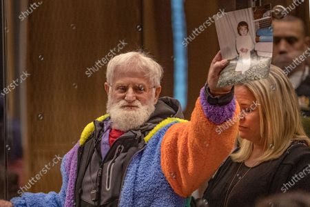 John Milne holds a photograph of his son, Sayyad Milne, who was killed as his daughter, Brydie Henry, right, watches during his victim impact statement during the sentencing hearing for Australian Brenton Harrison Tarrant at the Christchurch High Court after Tarrant pleaded guilty to 51 counts of murder, 40 counts of attempted murder and one count of terrorism in Christchurch, New Zealand, . More than 60 survivors and family members will confront the New Zealand mosque gunman this week when he appears in court to be sentenced for his crimes in the worst atrocity in the nation's modern history