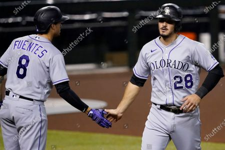 Colorado Rockies' Nolan Arenado (28) is greeted by Josh Fuentes (8) after scoring on a base hit by Matt Kemp during the first inning of a baseball game, in Phoenix
