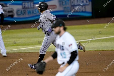 Colorado Rockies' Garrett Hampson rounds the bases after hitting a solo home run as Arizona Diamondbacks starting pitcher Alex Young (49) look away during the fourth inning of a baseball game, in Phoenix