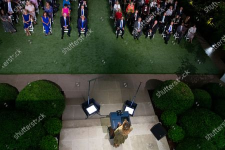 Stock Image of First lady Melania Trump (Bottom) delivers a speech during the second night of the Republican National Convention, as United States President Donald J. Trump (Top C) looks on, in the Rose Garden of the White House in Washington, DC, USA, 25. Those sitting in the front row include, from left to right: Senior Counselor Kellyanne Conway, Karen Pence, US Vice President Mike Pence, US President Donald J. Trump, US Secretary of the Treasury Steven T. Mnuchin, US Secretary of the Interior David Bernhardt, US Secretary of Agriculture Sonny Perdue, US Secretary of Commerce Wilbur L. Ross, Jr., and US Secretary of Housing and Urban Development (HUD) Ben Carson. Also seated in the second row behind the President and Vice President are Melania's parents Amalija Knavs, and Viktor Knavs.